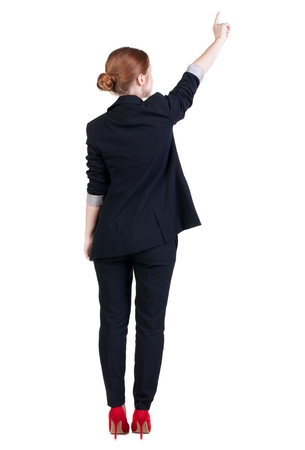 1 person: Back view of young redhead business woman pointing at wall. beautiful girl in dark suit. Rear view people collection. backside view of person. Isolated over white background.