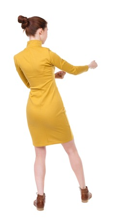 back view of standing woman pulling a rope from the top or cling to something.  Rear view people collection.  backside view of person.  Isolated over white background. Girl in mustard strict dress pulls the rope on the right