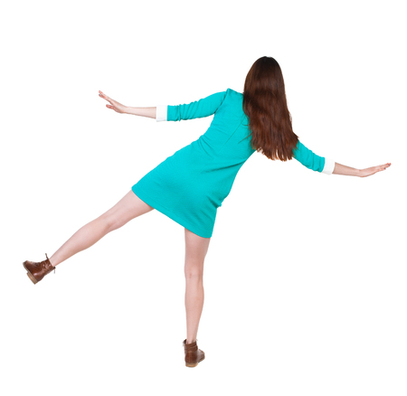 Back view woman Balances waving his arms.   Standing young girl in dress. Rear view people collection.  backside view of person.  Isolated over white background. The girl in a blue dress with brown shoes keeps the balance standing on one leg.
