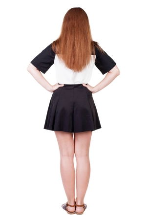 Back view of young redhead woman pointing at wall. beautiful girl in dress. Rear view people collection. backside view of person. Isolated over white background. Stock Photo