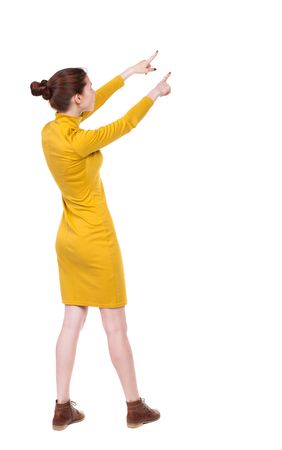 Back view of  pointing woman. beautiful girl. Rear view people collection.  backside view of person.  Isolated over white background. Girl in mustard strict dress stands sideways and two hands shows...