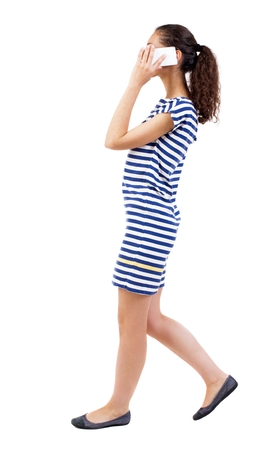 enthusiastically: a side view of a woman walking with a mobile phone. beautiful curly girl in motion.  backside view of person.  Rear view people collection. Isolated over white background.  African-American woman in a striped dress on the move enthusiastically talking on