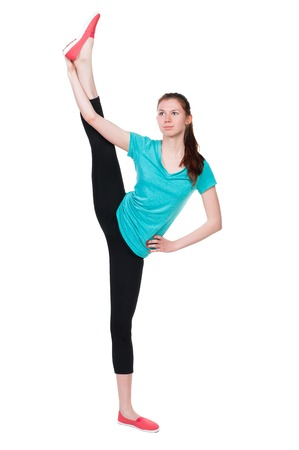 back view of standing young beautiful  woman in sportswear involved in Pilates. Rear view people collection.  backside view of person.  Isolated over white background. A girl stands with his legs above his head. Stock Photo