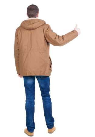parka: Back view of handsome man in winter jacket  shows thumbs up. Standing young guy in parka. Rear view people collection.  backside view of person.  Isolated over white background.