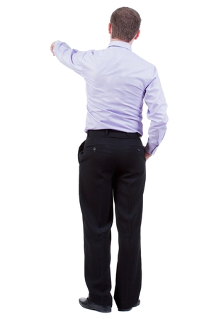 Back view of pointing business man. gesticulating young guy in black suit. Rear view people collection.  backside view of person.  Isolated over white background. office worker in a shirt and trousers powerfully indicates something Side