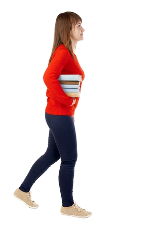 Girl comes with  stack of books.back view. Rear view people collection.  backside view of person.  Isolated over white background. Stock Photo