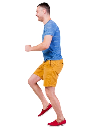 Back view of running man in t-shirt and shorts. Walking guy in motion. Rear view people collection. Backside view of person. Isolated over white background. Stock Photo
