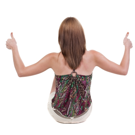 peron: back view of siting young blonde  woman showing thumb up.  Rear view people collection.  backside view of person.  Isolated over white background