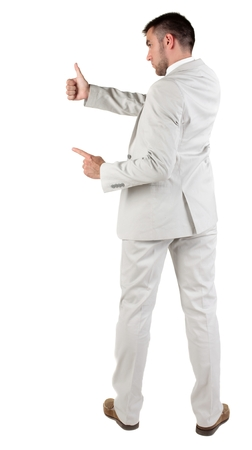 Back view of young business man in white suit going thumb up, isolated on white background. Rear view.Showing of positive emotions with OK sign concept .