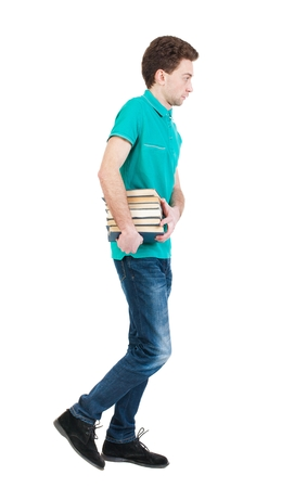 Back view of going  handsome man carries a stack of books. walking young guy . Rear view people collection.  backside view of person.  Isolated over white background. Sad man in a green T-shirt goes to the left with a stack of books.