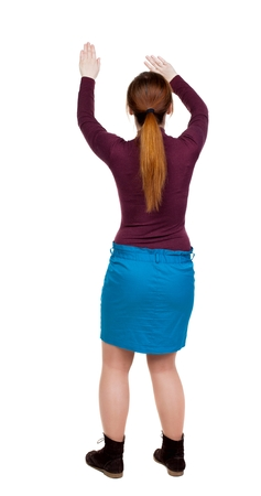 back view of dancing young beautiful  woman. girl  watching. Rear view people collection.  backside view of person.  Isolated over white background. girl in a blue skirt and a burgundy sweater waving his arms with open palms.