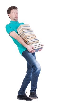 front view of going  handsome man carries a stack of books. walking young guy . Rear view people collection.  backside view of person.  Isolated over white background. Thin student carries a heavy stack of books. Stock Photo