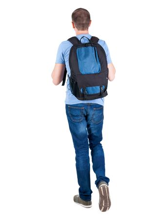back view of walking  man  with backpack.  brunette guy in motion. backside view of person.  Rear view people collection. Isolated over white background. young man goes to side of a rolling travel bag on wheels Stock Photo