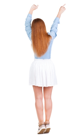 Back view of  joyful woman celebrating victory hands up. Rear view people collection. backside view of person. Isolated over white background. slender redhead in a dress shows symbol of success or hitchhiking