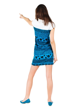 Back view of young brunette woman pointing at wall . beautiful girl in blue dress showing gesture. Rear view. Isolated over white background.