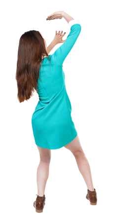 back view woman in a dress protects hands from what is falling from above. Rear view people collection.  backside view of person.  Isolated over white background. The girl in a blue dress with brown boots closes her face against the danger from above. Stock Photo