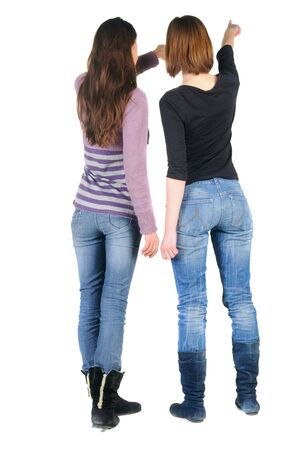 Two women pointing at wall. Rear view. Isolated over white.