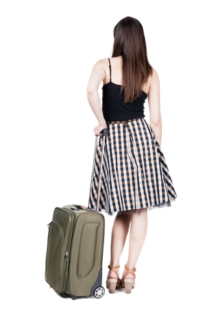 stylishly: Back view of stylishly dressed brunette business woman with suitcase looking up. Standing young girl. Rear view people collection.  backside view of person.  Isolated over white background. languid girl in heels looks into the distance Stock Photo