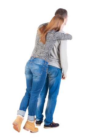 Back view of young embracing couple (man and woman) hug and look into the distance. beautiful friendly girl and guy together. Rear view people collection.  backside view of person.  Isolated over white background. Girl standing on tiptoes and hugs from be Stock Photo