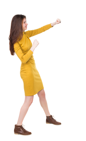 skinny woman funny fights waving his arms and legs. Rear view people collection.  backside view of person.  Isolated over white background. Girl engineer in the yellow dress standing right side and hit his left hand. Stock Photo