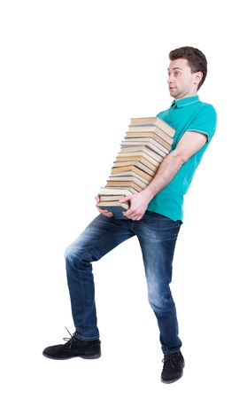 treading: Back view of going  handsome man carries a stack of books. walking young guy . Rear view people collection.  backside view of person.  Isolated over white background. High school student carries a book in the library. Stock Photo
