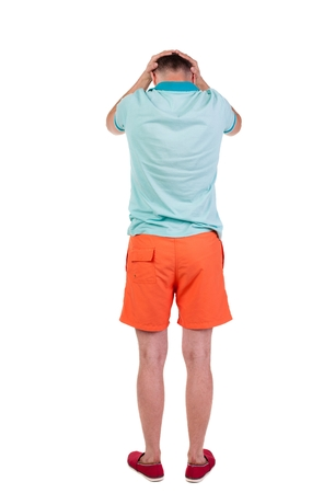 watching horror: Back view of angry young man in shorts and t-shirt. Rear view. isolated over white. backside view of person.  Rear view people collection. Isolated over white background. Foto de archivo
