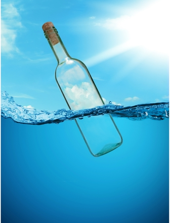 The concept of a bottle with a message. without letters. Empty bottle floating on the waves. Stock Photo