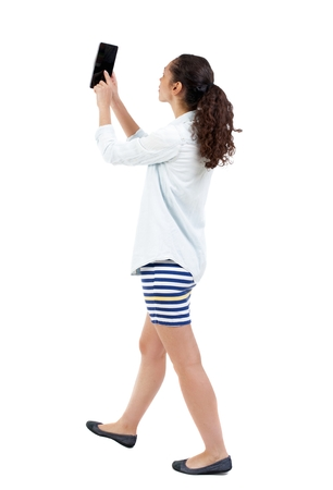concentration: a side view of a woman walking with a tablet PC is in the hands of beautiful curly girl in motion.  backside view of person.  Rear view people collection. Isolated over white background.  African-American is photographing tablet.