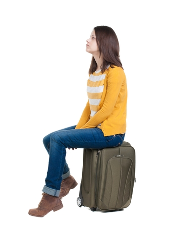 side view of walking  woman  in cardigan sits on a suitcase. beautiful  girl in motion.  backside view of person.  Rear view people collection. Isolated over white background.