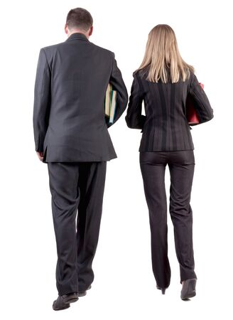 Back view of walking business team. Going young couple in suit with books go get an education. Rear view people collection. backside view of person. Isolated over white background Stock Photo