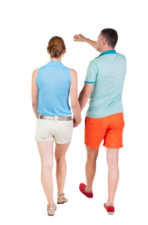 treading: Back view of walking young couple (man and woman) pointing. going tourists in shorts considering attractions. Rear view people collection. backside view of person. Isolated over white background