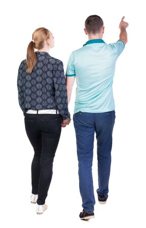 Back view of walking young couple (man and woman) pointing. Rear view people collection. backside view of person. Isolated over white background Stock Photo