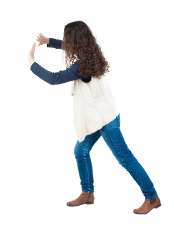 pushes: back view of woman pushes wall. Isolated over white background. Rear view people collection. backside view of person. curly girl put her hands on the obstacle. A girl in a white tank top is pushing the wall in front of him.
