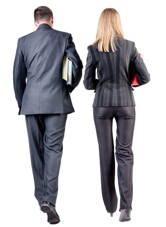 Back view of  walking business team. Going young couple (man and woman) with books.  beautiful friendly girl and guy in suit together. Rear view people collection.  backside view of person.  Isolated over white background. Stock Photo
