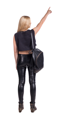 Back view of  pointing woman with a backpack. beautiful girl. Rear view people collection.  backside view of person.  Isolated over white background. Blonde in leather pants standing with backpack standing and shows his hand up.