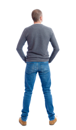 Back view of man in jeans. Standing young guy. Rear view people collection.  backside view of person.  Isolated over white background.  A guy in a gray sweater standing with folded hands in his pockets