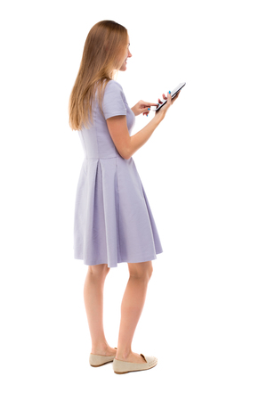 back view of standing young beautiful  girl with tablet computer in the hands of. girl  watching. Rear view people collection.  backside view of person.  Isolated over white background.Skinny girl in a blue dress and working on the tablet.