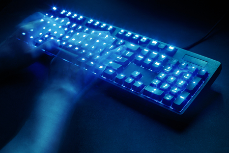 illuminated keyboard. male hands typing on a computer. hacker or programmer at work. on a black background. view from above. Stock Photo