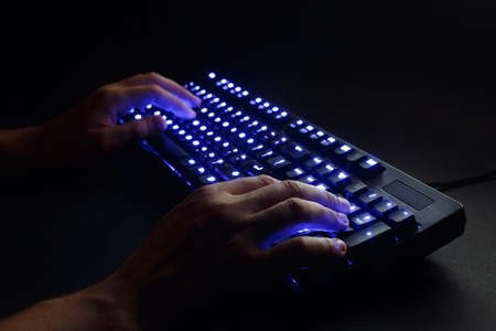 ergonomic keyboard: illuminated keyboard. male hands typing on a computer. hacker or programmer at work. on a black background.blue toning. Stock Photo