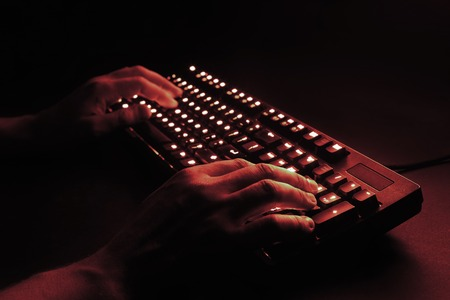 illuminated keyboard. male hands typing on a computer. hacker or programmer at work. on a black background. red tint. Stock Photo