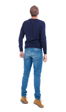 tiptoes: Back view of a curious guy who stood on tiptoes, and peering up. tanding young guy. Rear view people collection.  backside view of person.  Isolated over white background.  Man in warm jacket stood on tiptoe. Stock Photo