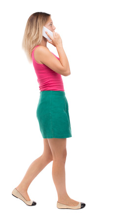 misses: side view of a woman walking with a mobile phone. back view ofgirl in motion.  backside view of person.  Rear view people collection. Isolated over white background. Girl in a green skirt misses talking on the phone.