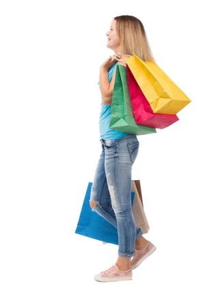 back view of going  woman  with shopping bags . beautiful girl in motion.  backside view of person.  Rear view people collection. Isolated over white background. The blonde in a blue sweater misses with colored blocks on the shoulder