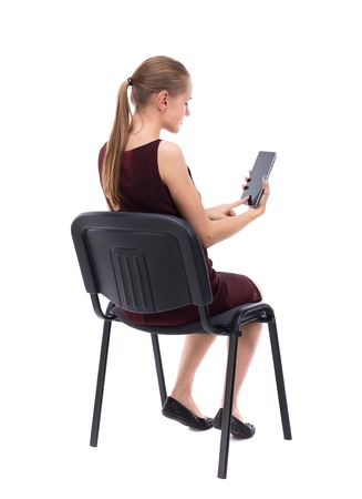 girl in burgundy dress: back view of woman sitting on chair and looks at the screen of the tablet.  Rear view people collection.  backside view of person.  Isolated over white background. A girl in a burgundy dress sitting on a chair and reading a phone. Stock Photo