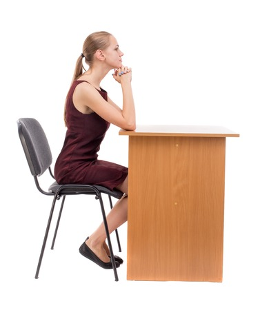 girl in burgundy dress: back view of woman sits by the table and looks.  Rear view people collection.  backside view of person.  Isolated over white background. A girl in a burgundy dress sitting at the table.