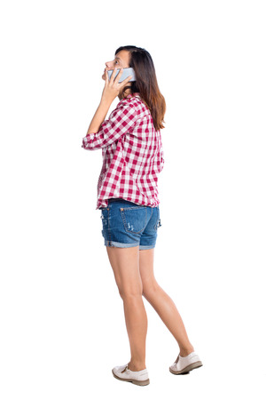 back view of a woman talking on the phone.  backside view of person.  Rear view people collection. Isolated over white background. Girl in shorts on the phone Stock Photo