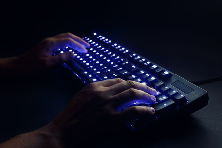ergonomic keyboard: illuminated keyboard. male hands typing on a computer. hacker or programmer at work. on a black background.