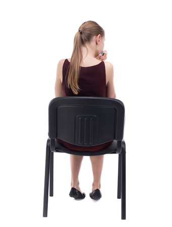 back view of young beautiful  woman sitting on chair.  girl  watching. Rear view people collection.  backside view of person.  Isolated over white background. A girl in a burgundy dress thoughtfully sits on a chair. Stock Photo