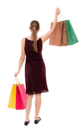 girl in burgundy dress: back view of woman with shopping bags . beautiful brunette girl in motion.  backside view of person.  Rear view people collection. Isolated over white background. A girl in a burgundy dress lifted in hand with shopping bags. Stock Photo