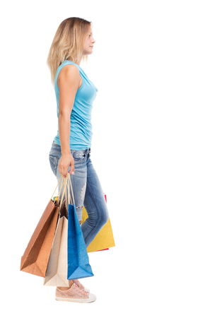 back view of going  woman  with shopping bags . beautiful girl in motion.  backside view of person.  Rear view people collection. Isolated over white background.  The blonde in a blue sweater misses with colored bags